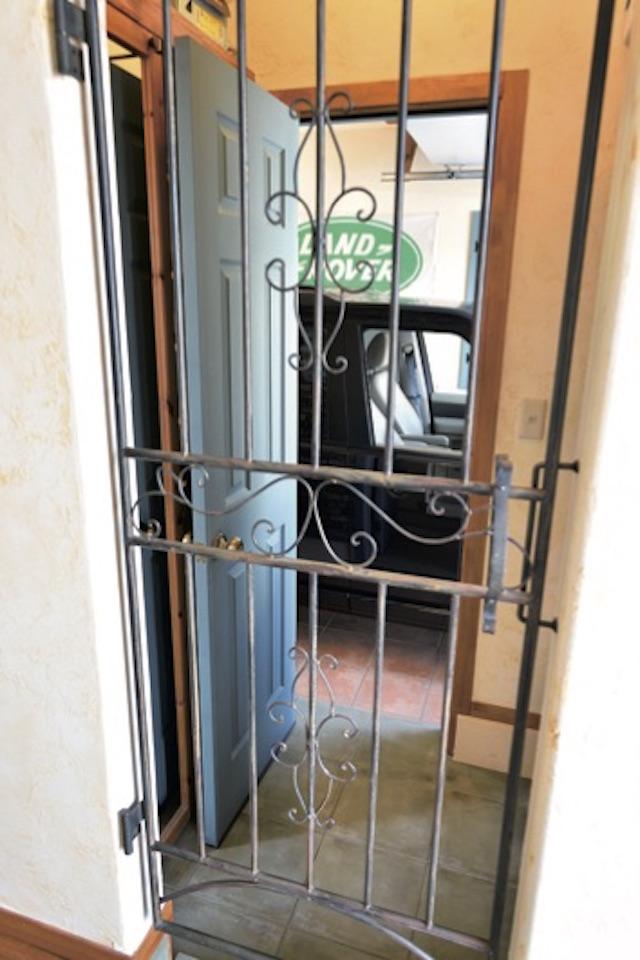 ▲玄関からガレージへ続く動線。鉄格子の扉が旧い屋敷風の趣を醸し出している