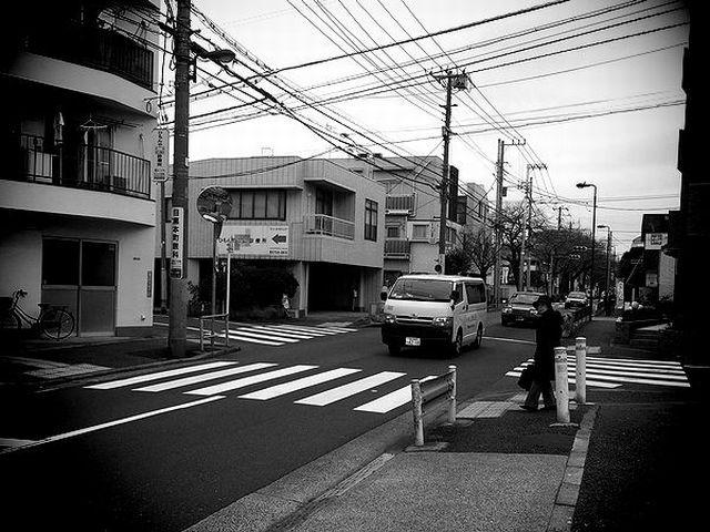 ▲筆者自宅近所の信号機のない交差点。中年女性が横断歩道を渡ろうとしているが、筆者が見ている間、停止した車は残念ながら皆無だった