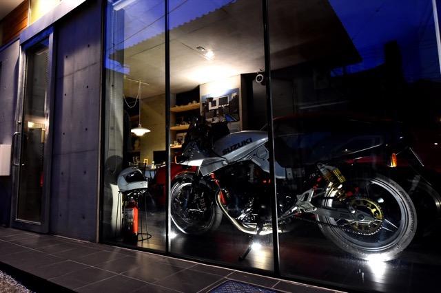 ▲左手のドアが玄関。横の壁面は広いガラス窓で、見せるガレージとしてライトアップされた様子に、思わず立ち止まって見入ってしまう