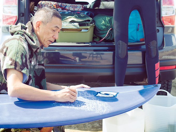 ▲着替えがしやすいタオル地のポンチョをはおり、ショートボードにワックスを塗る