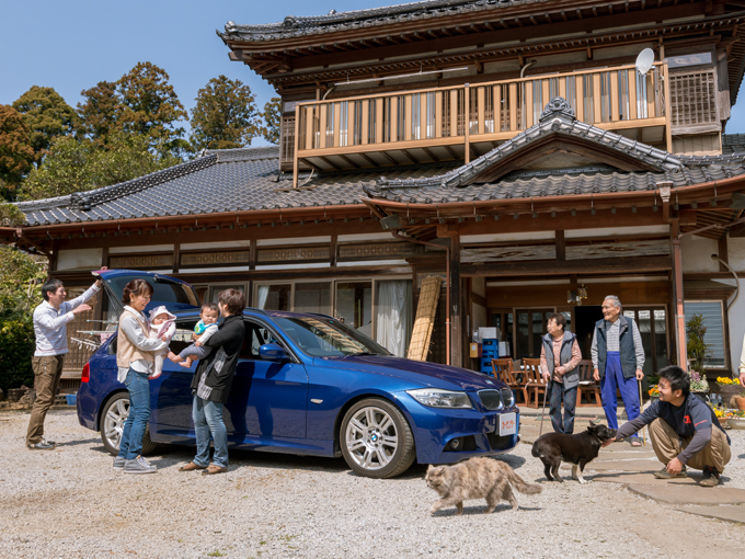 ▲立派な玄関の前にて「いらっしゃい! よく来たね」の瞬間。車も家族の一員のようだ