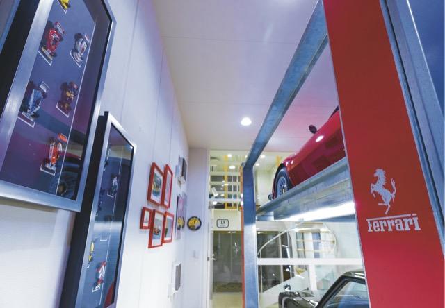 ▲ミニカーや絵画の他、リフトにはレッドのアクセントを入れるなどガレージはじつに華やかな雰囲気