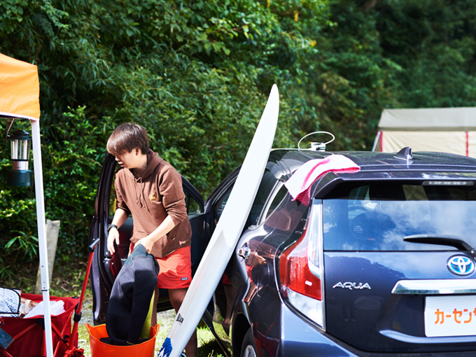▲サーフィン後、テントに戻ってきた千葉さん。アクアに立てかけて、道具を干す
