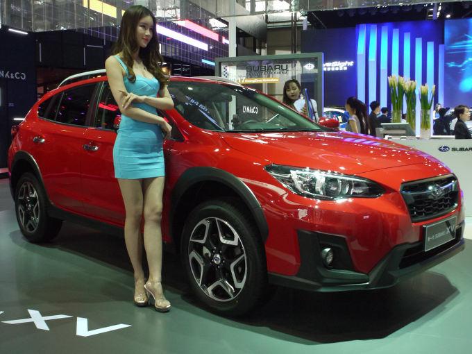 """▲スバル車の中でも、中国での量販が期待できるモデルがXVだ。展示車は""""全駆動(AWD)尊貴版アイサイト""""というグレード。多くの人たちが、水平対向エンジンを興味深げに見ていた。ヒールを履いているとはいえ、写真のモデルさんの身長が気になる"""