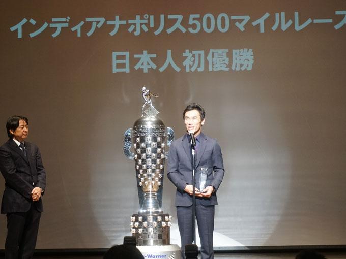 ▲巨大なトロフィーと共に登場した佐藤琢磨選手。「夢にも思わなかった壇上に立ててうれしく思います」と喜びのコメント