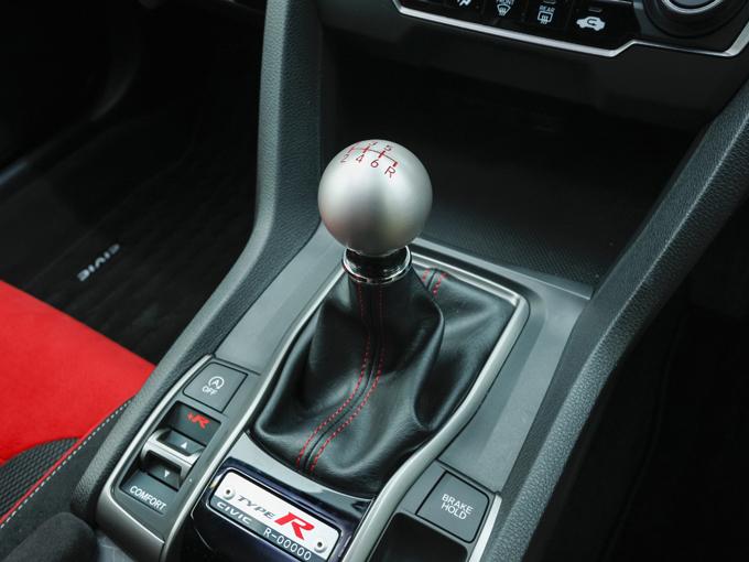 ▲扱いやすい球形のチタン製シフトノブを装着する6MT。操作感も本気のスポーツカーだと思える剛性を感じられるフィーリングだ。すぐ横にはブレーキホールドスイッチ、走行モード切替えスイッチなどが配置される。TYPE-Rにはシリアルナンバーのプレートが付く(写真は世に流通することのない広報車のため00000となっている)