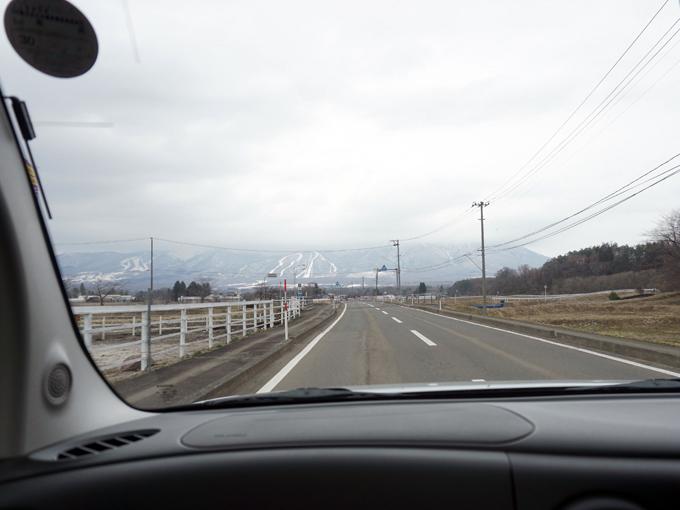 ▲中心部から少し離れると田んぼや畑が広がる。奥に見えるスキー場にはまだ雪が残っていた