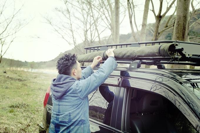 ▲スチール製ルーフラックの横にカーサイドタープを巻きつけている。自作のタープはミリタリーショップで購入した防水帆布製