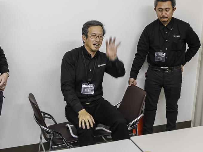 ▲テスト車両に装着されている同型の椅子を使って、マニアックな技術解説をできるだけわかりやすく紹介してくれている技術者の虫谷氏